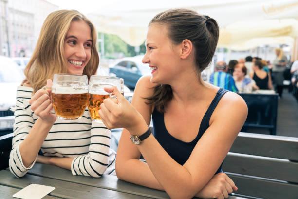 amigos do sexo feminino tomando cervejas no café ao ar livre - praga boémia - fotografias e filmes do acervo