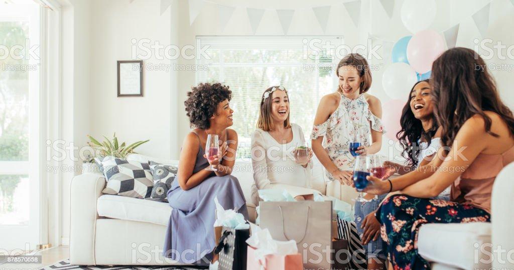 Female friends having drinks at baby shower stock photo