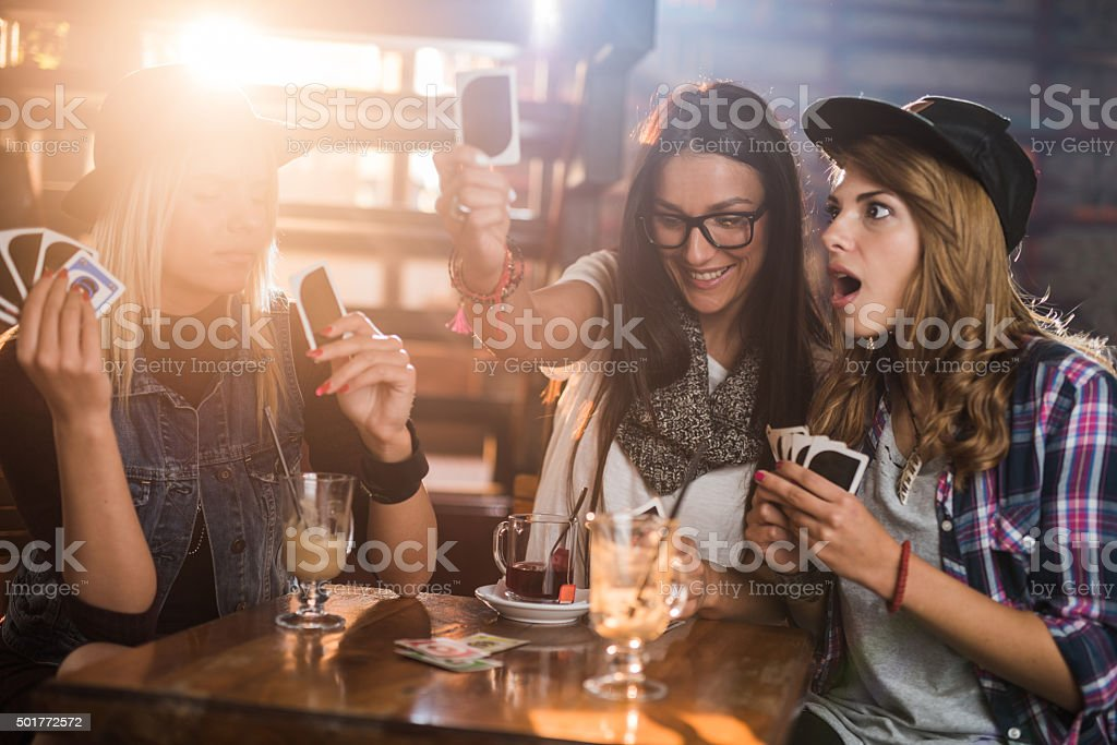 Female friends having fun in a cafe while playing cards. stock photo