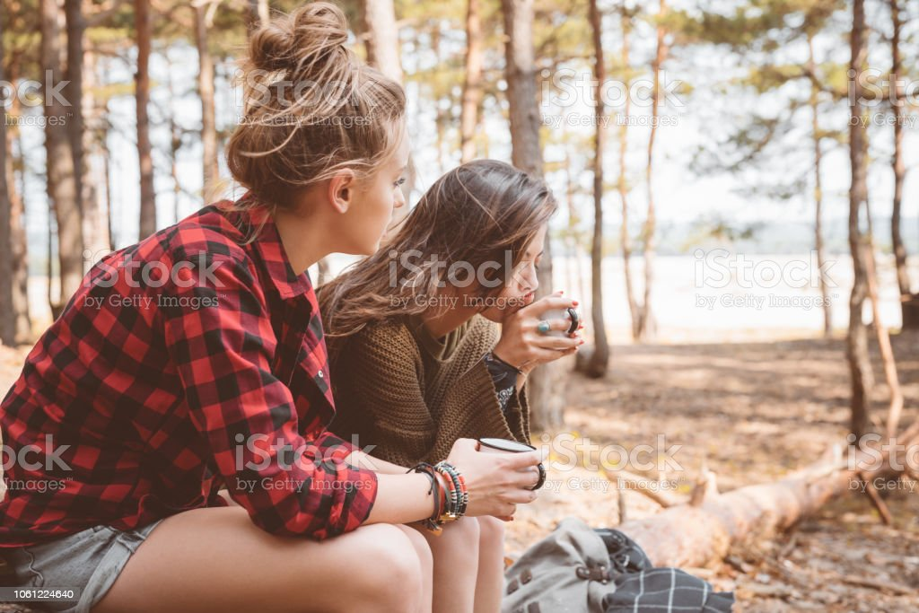 Female friends having picnic in the forest Outdoor shot of two young women resting in the forest, sitting on the fallen tree and drinking hot drink. Adolescence Stock Photo