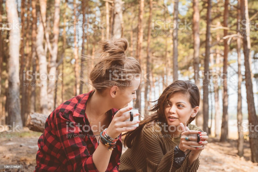 Female friends having picnic in the forest Outdoor shot of two young women having picnic in the forest, sitting on the fallen tree and drinking hot drink. Adolescence Stock Photo