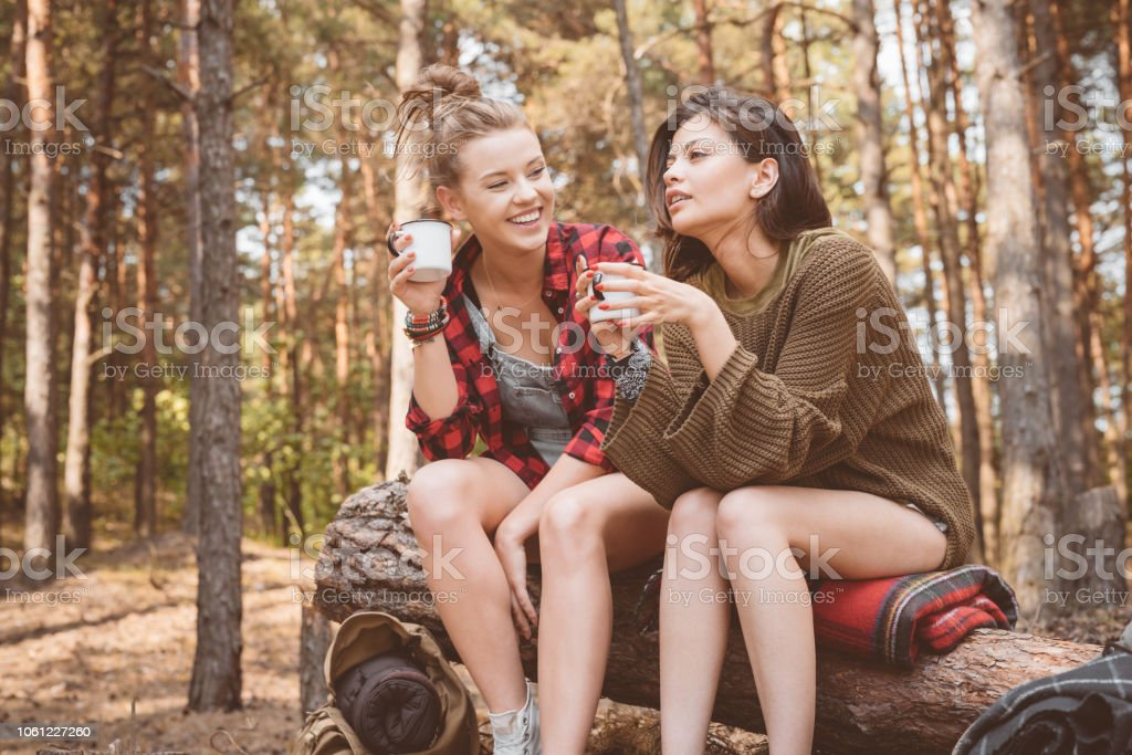 Female friends having picnic in the forest Outdoor shot of two happy young women having picnic in the forest, sitting on the fallen tree and drinking hot drink. Adolescence Stock Photo