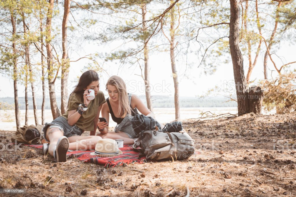 Female friends having picnic in the forest Outdoor shot of two young women having picnic in the forest, sitting on the ground, drinking hot drink and using smart phone. Adolescence Stock Photo