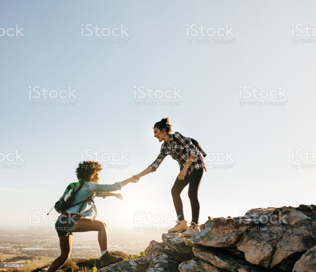 Female friends hiking help each other in mountains stock photo
