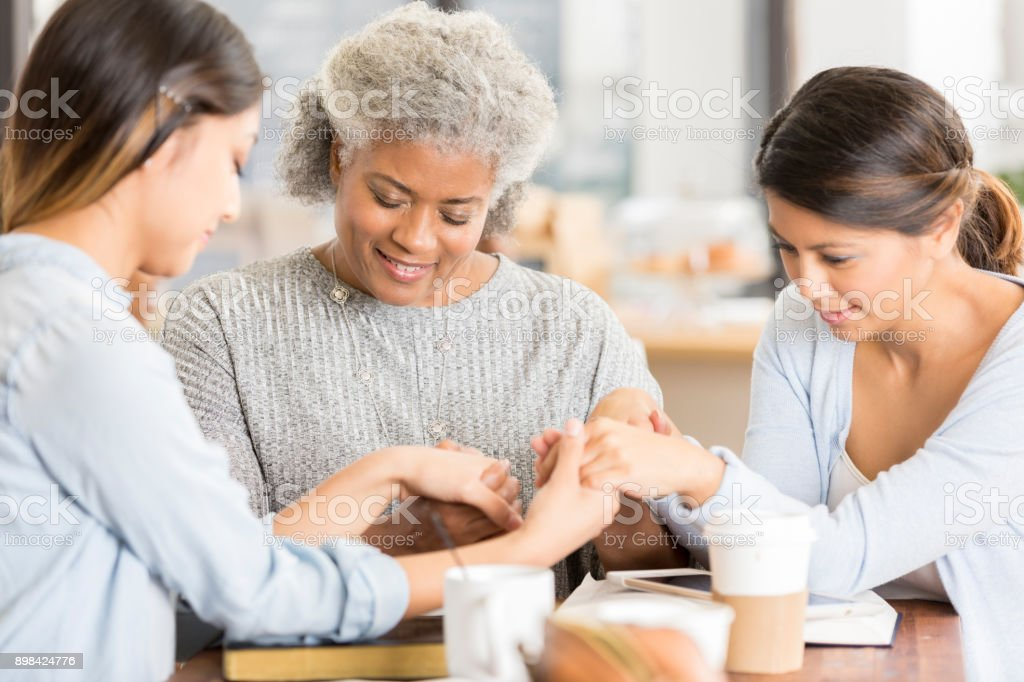 Female friends hold hands while praying stock photo
