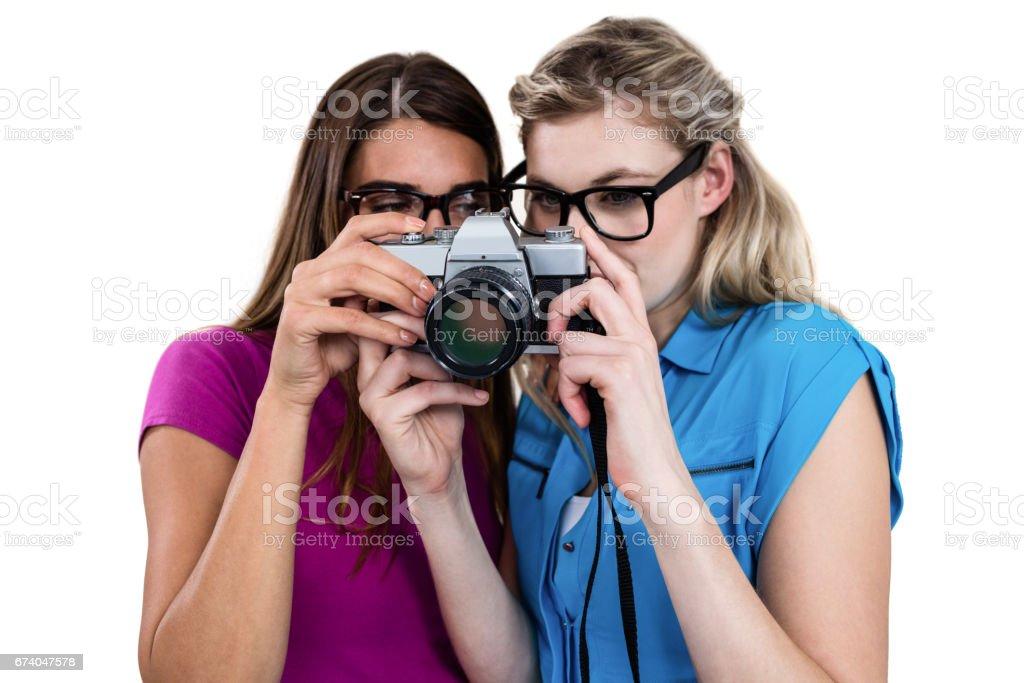 Female friends holding digital camera royalty-free stock photo