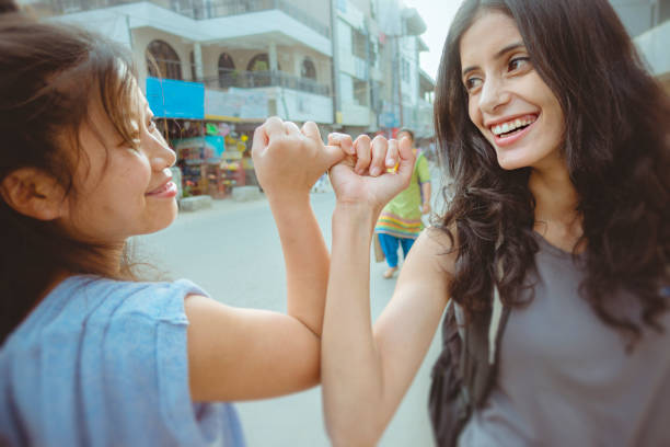 female friends hooking pinky promise with little fingers. - pinky promise stock photos and pictures