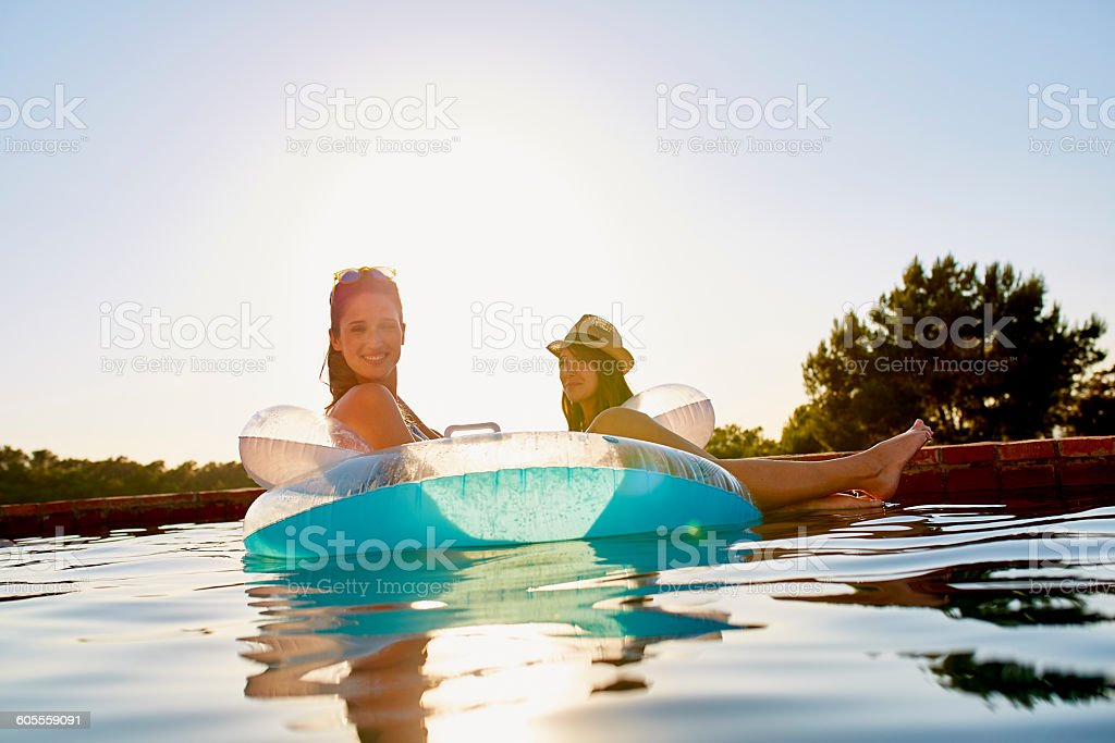 Female friends in inflatable ring floating on pool stock photo