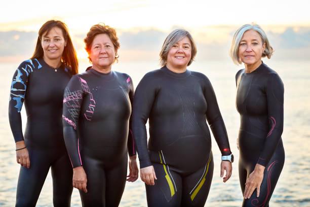 amigos do sexo feminino em wetsuits sorrindo na praia - body positive - fotografias e filmes do acervo