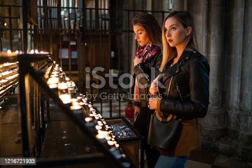 Female friends  lighting candle in church