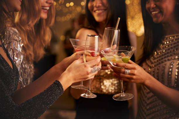 mujeres amigas hacen tostadas mientras celebran en la fiesta - cóctel fotografías e imágenes de stock