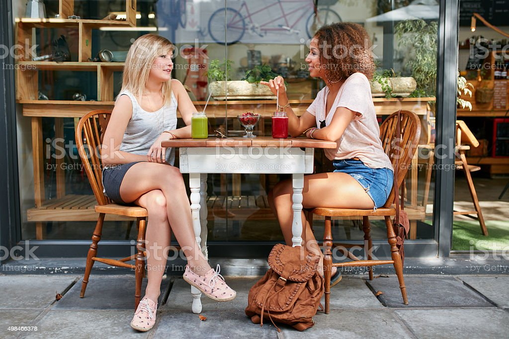 Female friends meeting at outdoor cafe stock photo