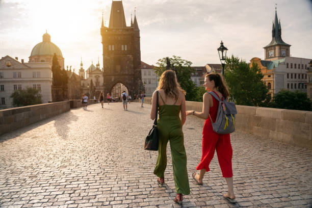 Female friends on holiday walking on Charles Bridge in Prague stock photo
