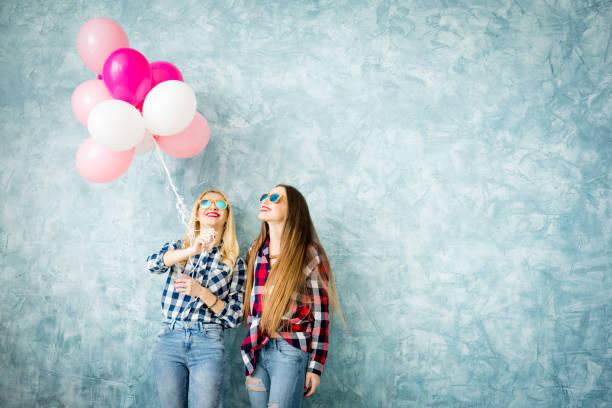 freundinnen auf dem blauen wand-hintergrund - ballonhose stock-fotos und bilder