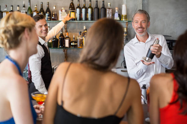 Female friends ordering drinks Female friends ordering drinks from barkeeper in restaurant old man working in a pub stock pictures, royalty-free photos & images