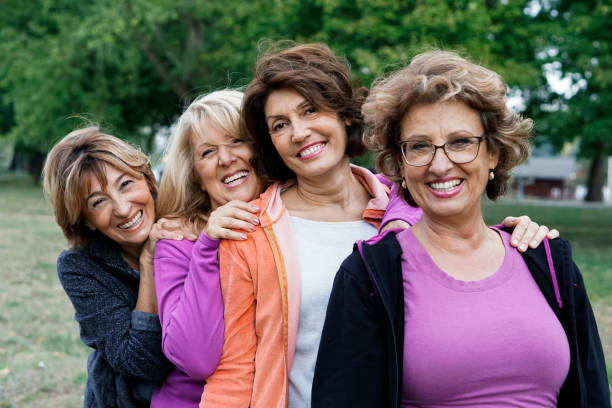 female friends over fifty exercising outdoors - four people stock photos and pictures