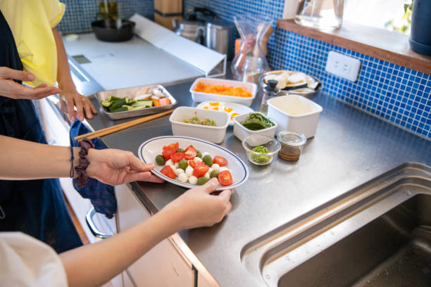 weibliche freunde bereiten salat in der küche - oliven wohnzimmer stock-fotos und bilder