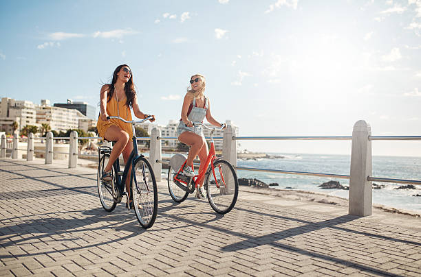 Female friends riding their bicycles on the promenade stock photo