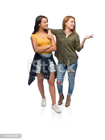 A full body image of two young woman hanging out together and turning over to look at a white copy space while one gestures with her hand.