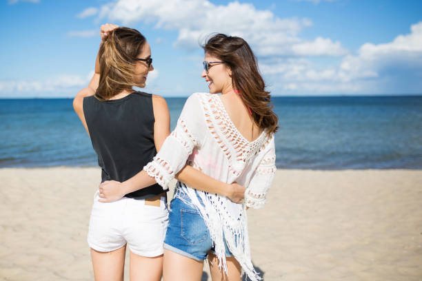 Female friends standing on beach embracing each other stock photo