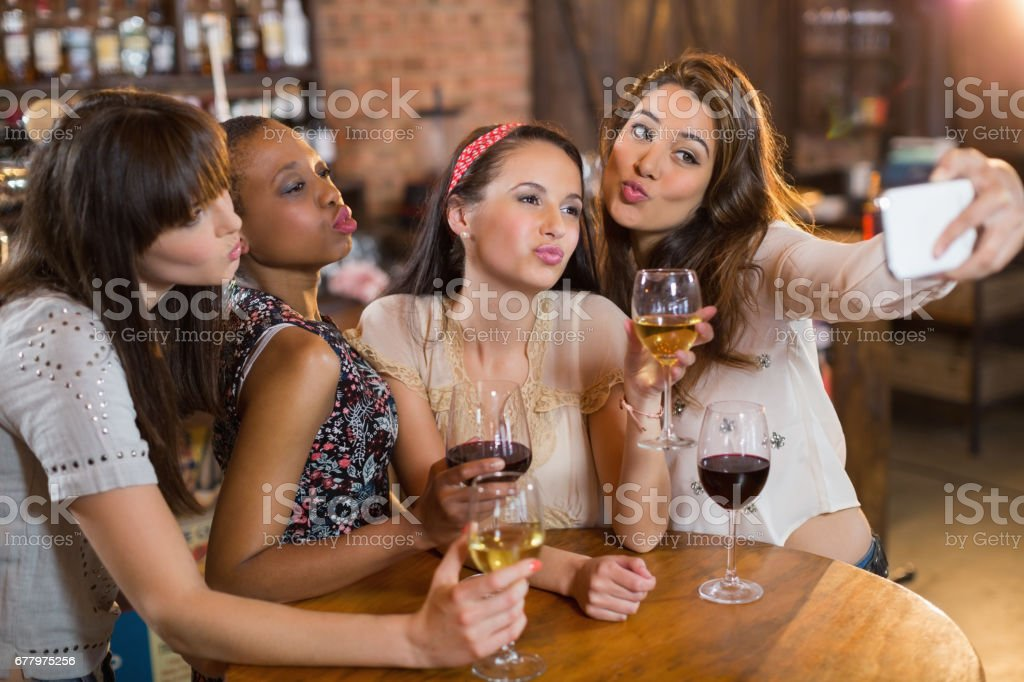 Female friends taking selfie while holding wineglasses royalty-free stock photo