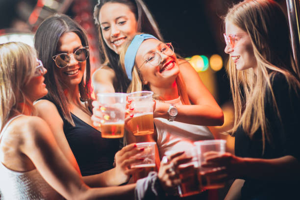 Female friends toasting with beer at the music festival stock photo