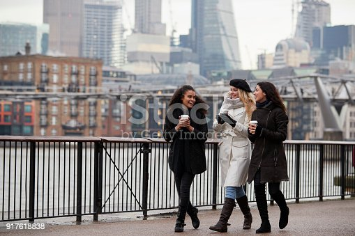 istock Female Friends Walk Along South Bank On Winter Visit To London 917618838