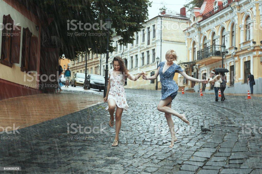 Female friends walk in the rain. stock photo