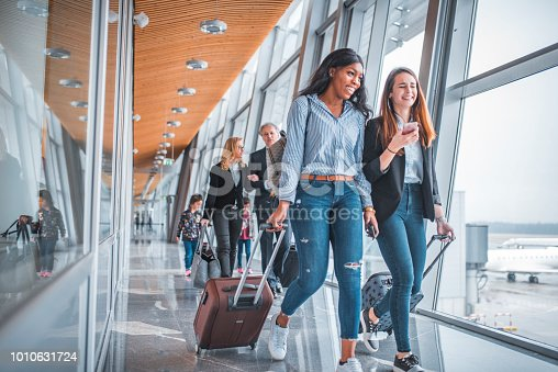 Young woman showing mobile phone to friend while business people walking in background. Passengers are with luggage by window at airport. They are on tiled floor.