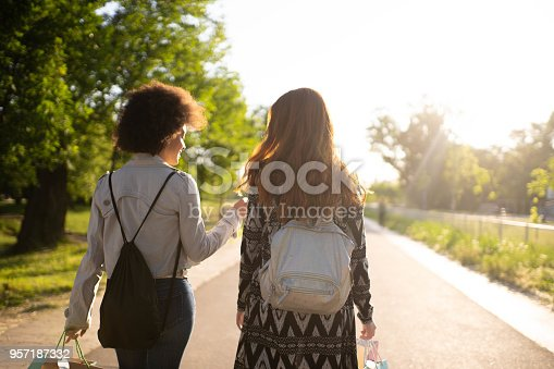 There are two woman age from 20 to 30. They are in public park, taking photos, shopping, and smiling