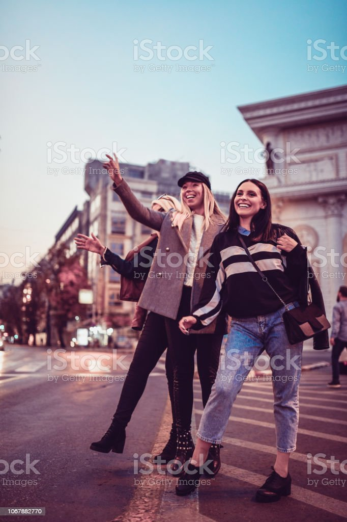 Female Friends Waving To a Taxi Car stock photo