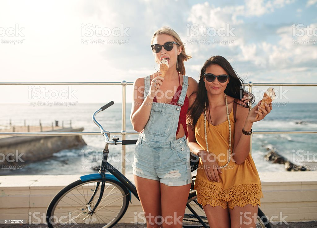 Female friends with a bike eating ice cream - Photo