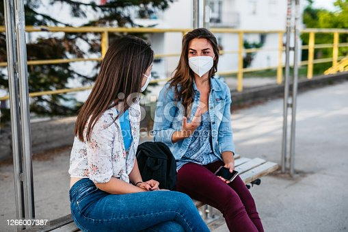 Young Caucasian female friends with a N-95 masks at a bus stop talking and waiting a bus.