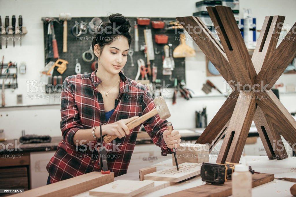 Female furniture designer at woodworking studio royalty-free stock photo