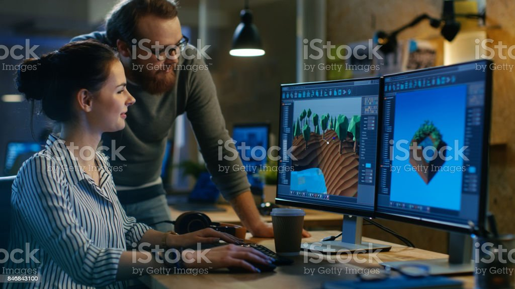 Female Game Developer Has Discussion with Male Project Manager While Working on a Game Level on Her Personal Computer with Two Displays. They Work in a Modern Loft Office Creative Environment. Female Game Developer Has Discussion with Male Project Manager While Working on a Game Level on Her Personal Computer with Two Displays. They Work in a Modern Loft Office Creative Environment. Adult Stock Photo