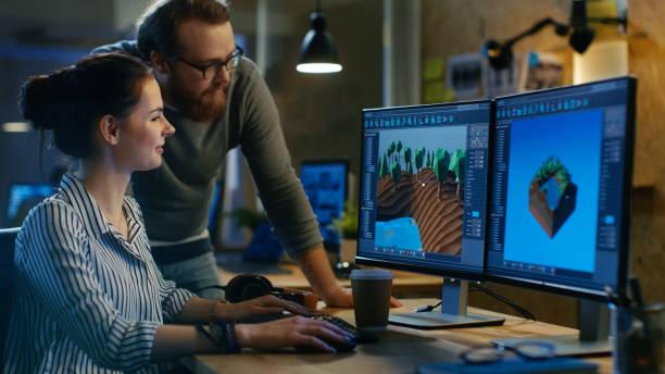 weibliche spieleentwickler hat diskussion mit männlichen projektmanager während der arbeit an einem spiel-level auf ihrem pc mit zwei displays. sie arbeiten in einem modernen loft büro kreativen umfeld. - projektmanager stock-fotos und bilder