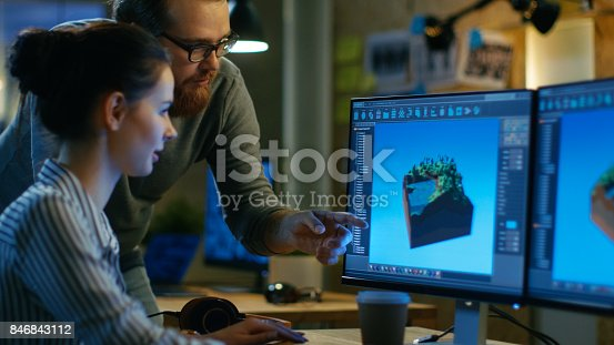 istock Female Game Developer Has Discussion with Male Project Manager While Working on a Game Level on Her Personal Computer with Two Displays. They Work in a Modern Loft Office Creative Environment. 846843112