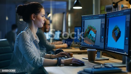 istock Female Game Developer Works on a Level Design on Her Personal Computer with Two Displays. She works in a Creative Office Space. 846843066