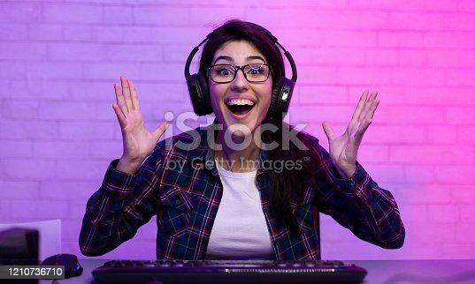 Joy Of Victory. Female Gamer Celebrating Winning Computer Game, Gesturing Shaking Hands Looking At Camera Sitting Indoor. Low Light