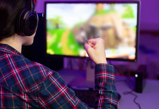 オンラインビデオゲームで勝つ女性ゲーマー - ゲーム ヘッドフォン ストックフォトと画像