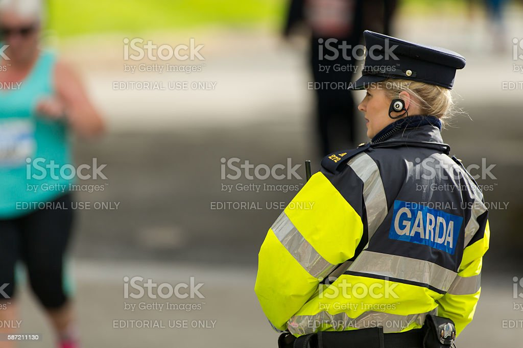 Female Garda Officer watching marathon runners stock photo