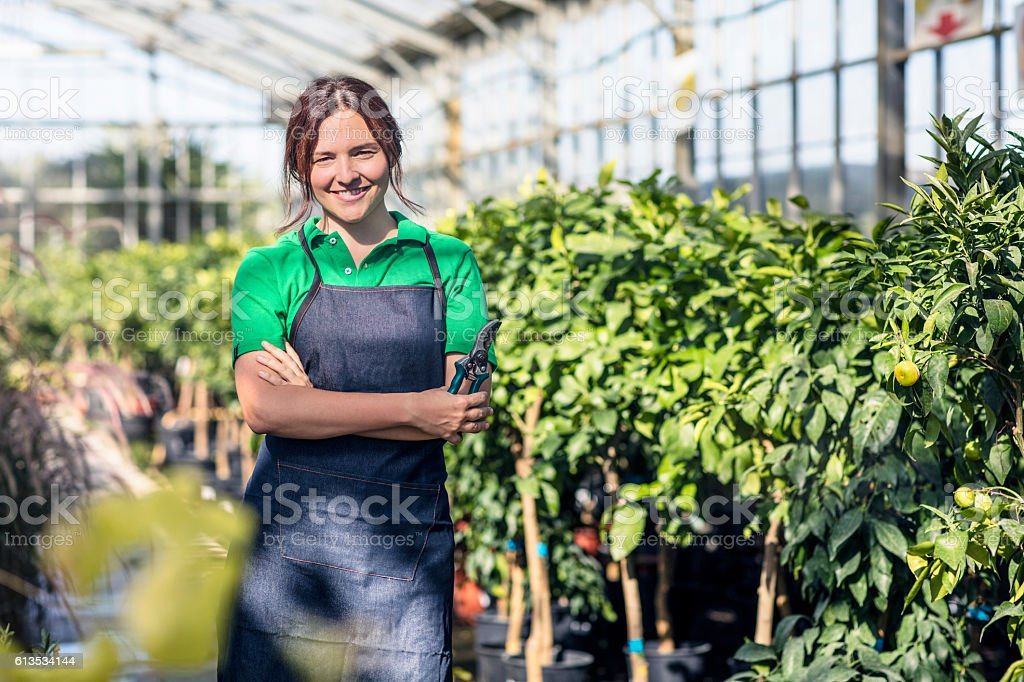 Female garden center worker with pruners stock photo