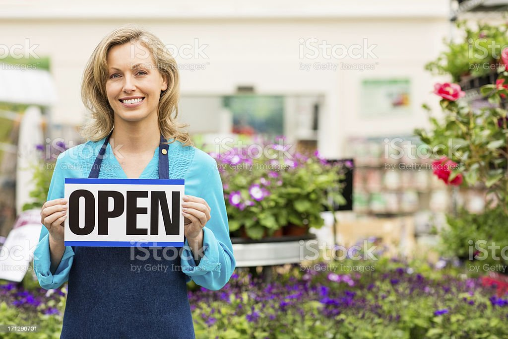 Female Garden Worker Holding an Open Signboard royalty-free stock photo