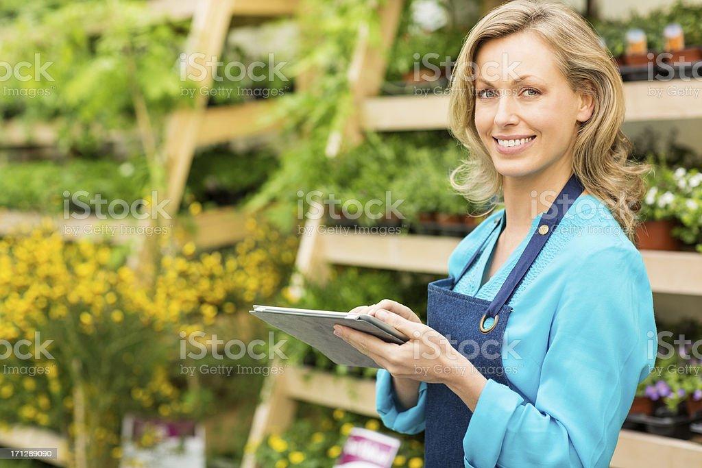 Female Garden Worker Using Digital Tablet stock photo