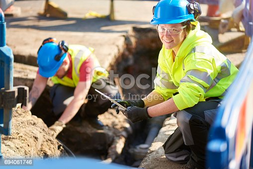 a female gas engineer holds a new gas valve as she and a colleague prepare to replace the old pipework in a residential uk street .