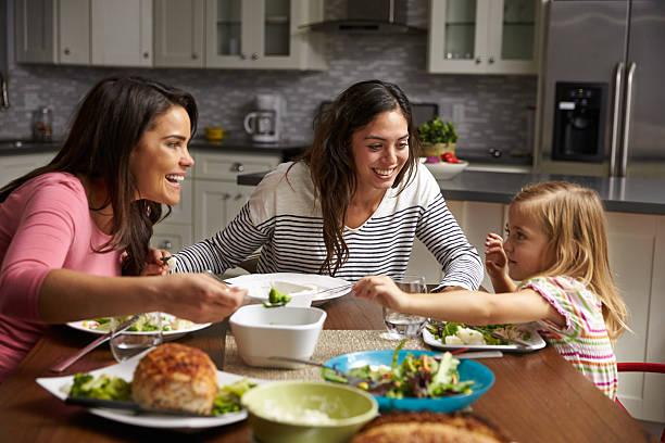 weibliche schwule paare und tochter in der küche, abendessen - küche aus paletten stock-fotos und bilder