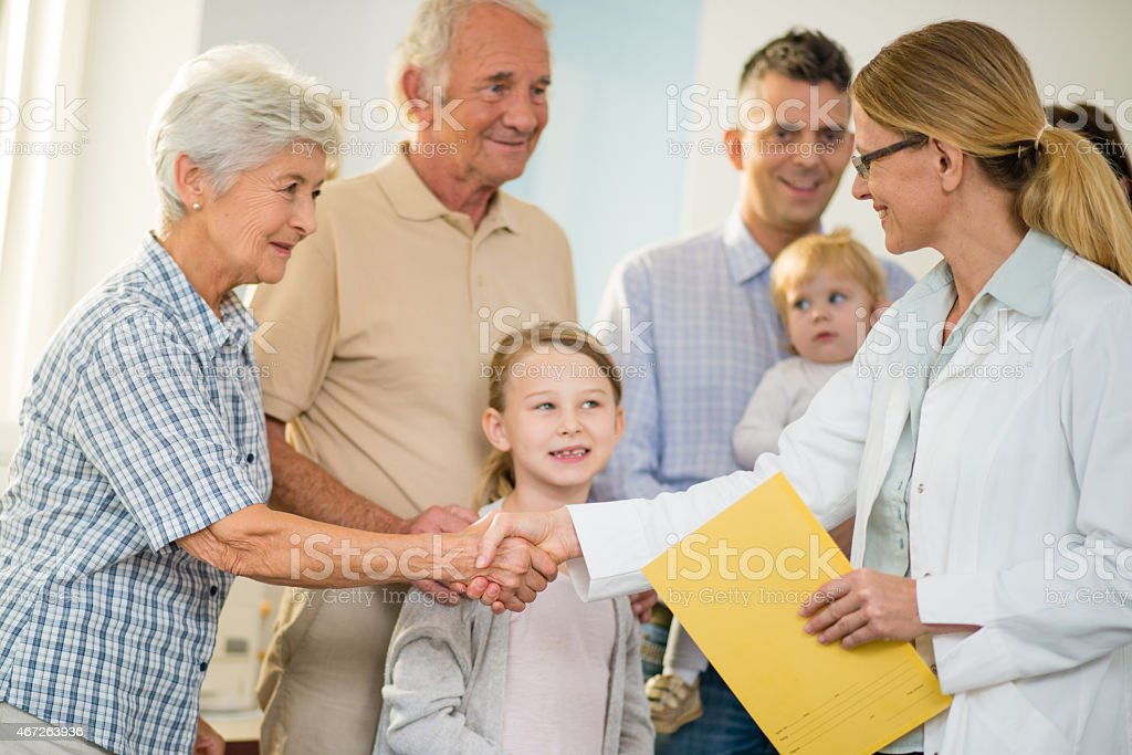Female General Practitioner Shaking Hands With Patients stock photo