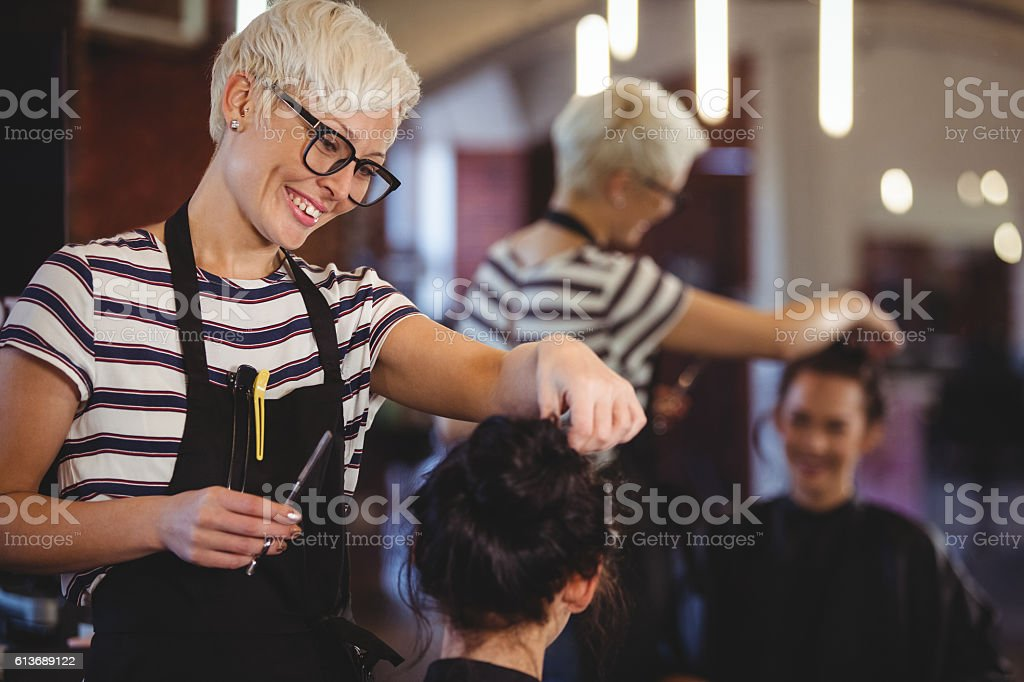 Female getting her hair trimmed stock photo