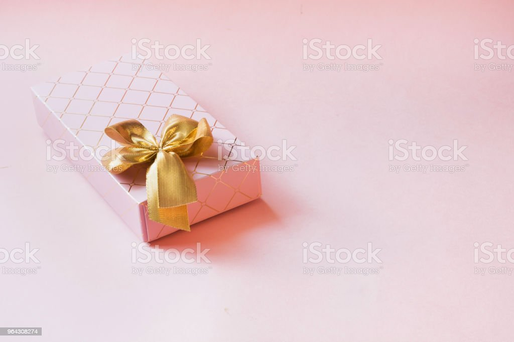 Female gift box with golden ribbon on punchy pastel pink. Birthday....