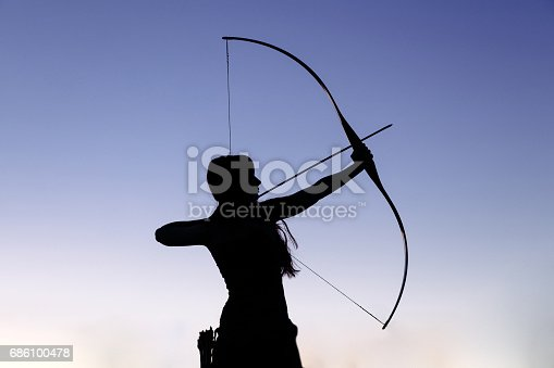 istock Female ginger hair archer shooting targets with her bow and arrow. Concentration, target, success concept 686100478